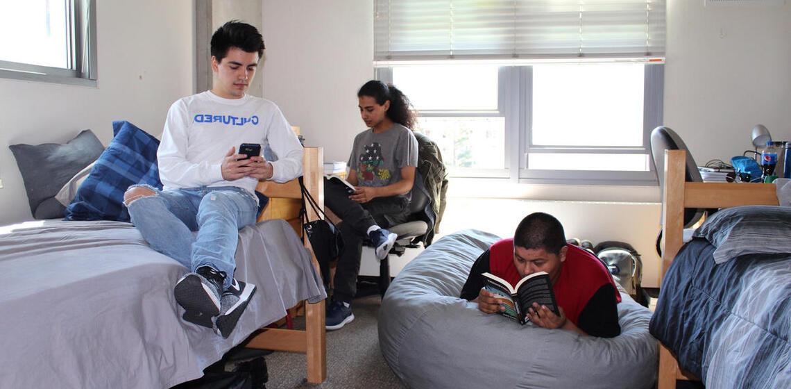 Group of three boys lounging around their dorm room