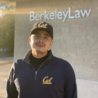 Student Emiliano Aguirre in a Berkeley branded zip up and hat standing in front of the Berkeley School of Law