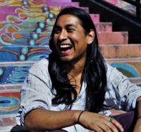 Student Jesus Nazario sitting on painted stairs laughing